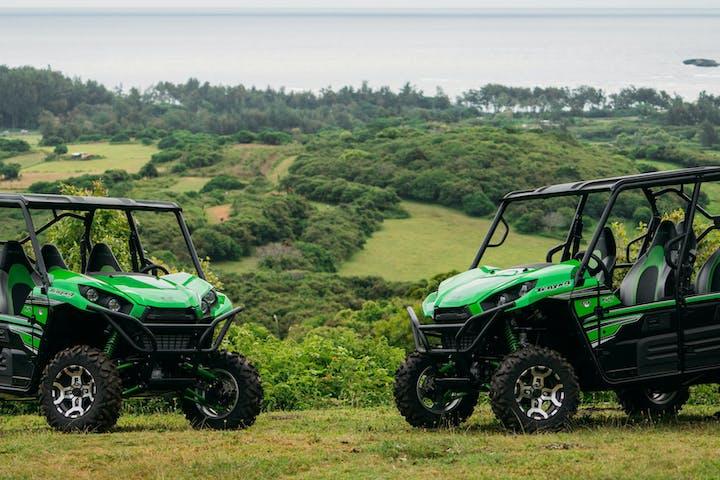 2 green off road vehicles overlooking the ocean background