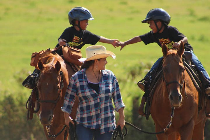 2 twin kids riding a pony with a woman guiding the horses