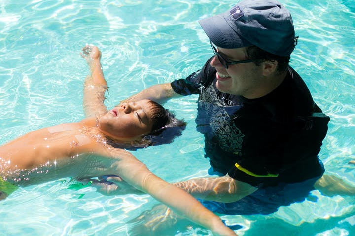 boy floating in water with help from instructor