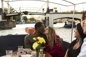 A romantic thing to do in Amsterdam is kissing under a bridge.