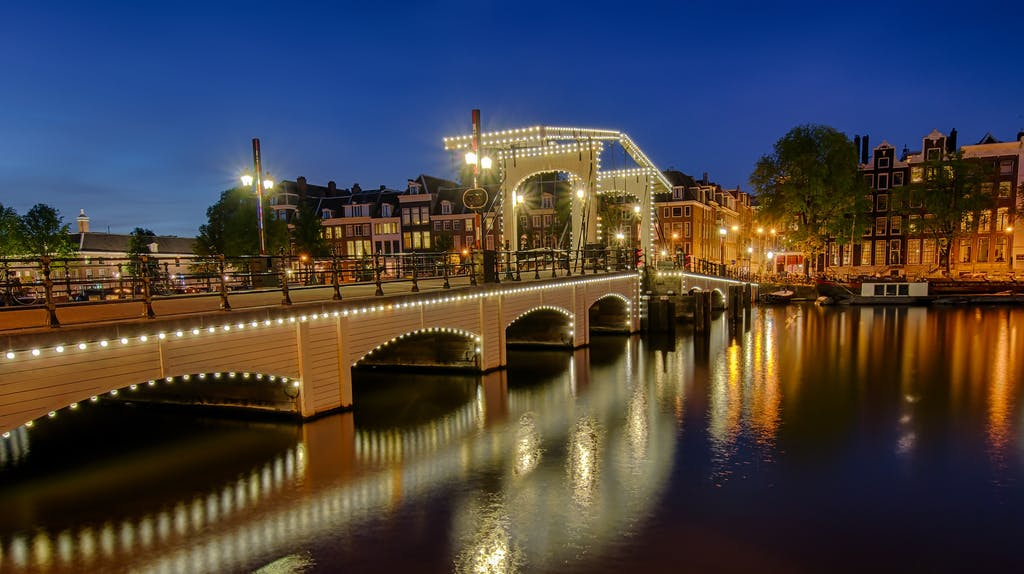 Skinny Bridge walk together by the canals during your Romantic trip to Amsterdam