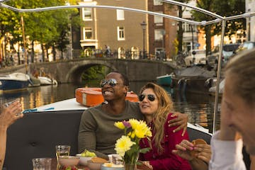 a couple sitting at a table on the romantic canal tour in Amsterdam