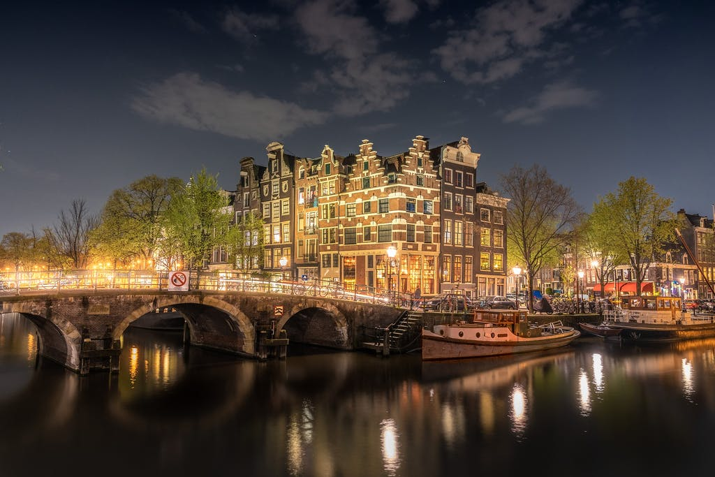 Night in Amsterdam, boats on the canals, bridge with lights and dutch houses