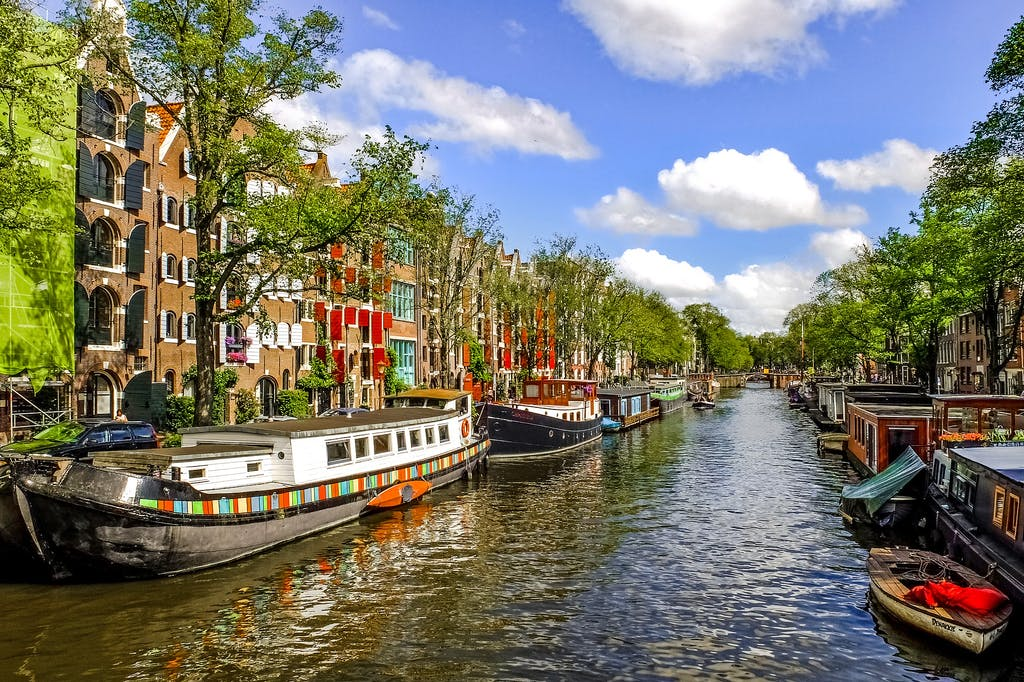 colourful boats on canals in Amsterdam and dutch houses in spring