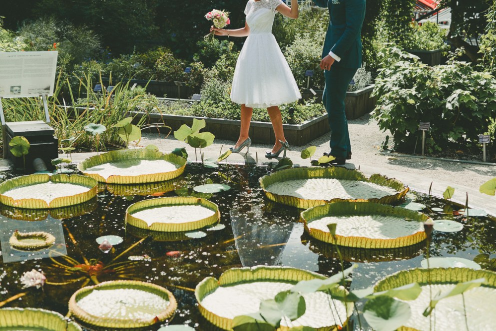 two people holding hands dancing in a botanical garden on their wedding