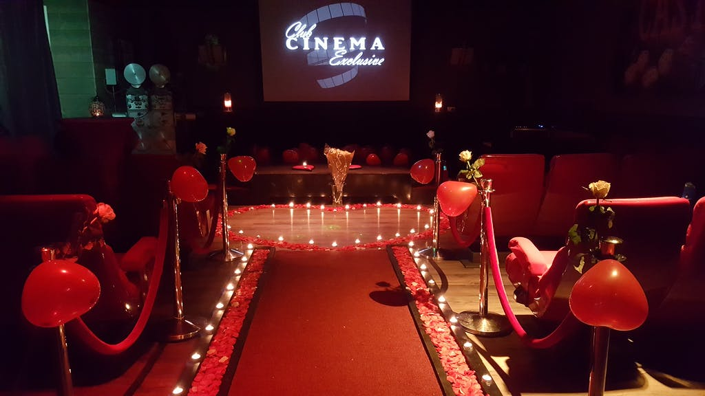 red balloons rose petals and candles in a cinema for a marriage proposal