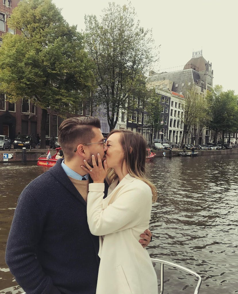 A man and a woman kissing happily on a boat tour in Amsterdam