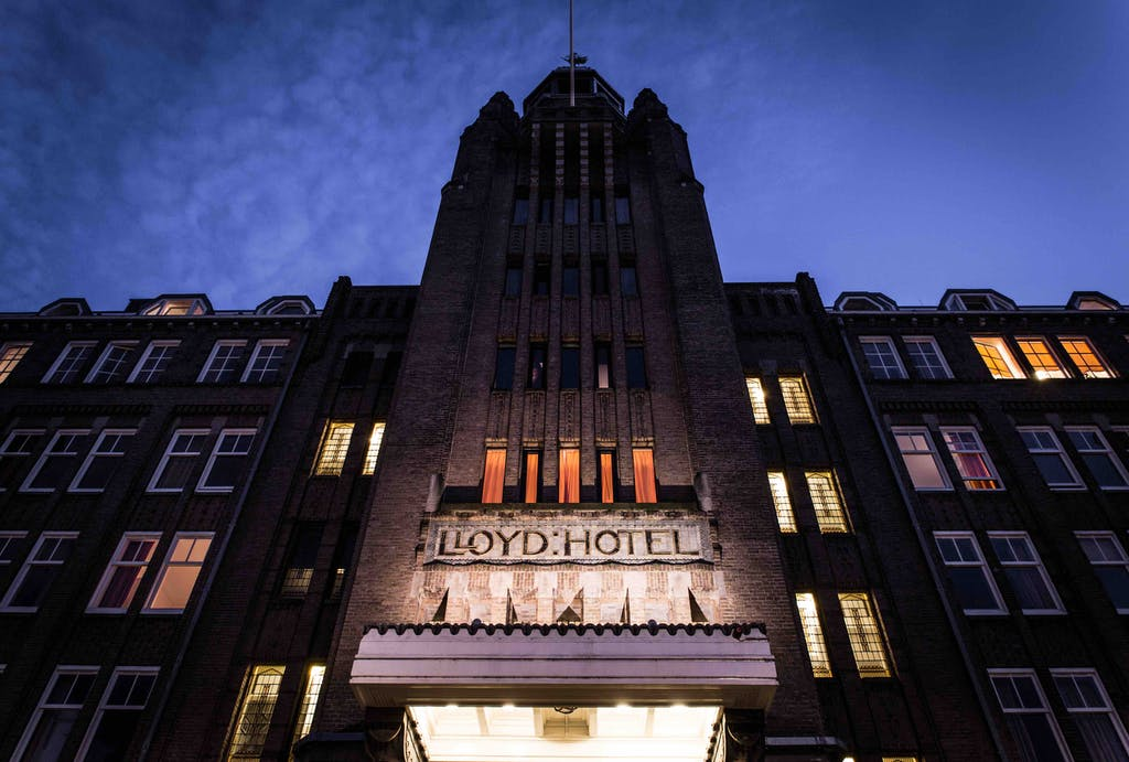 a large building with a clock tower lit up at night one of the romantic hotels in Amsterdam for your proposal