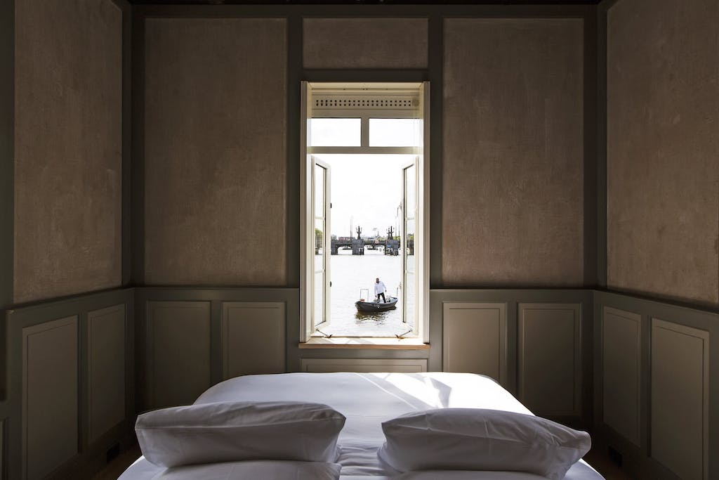 interieur of one of romantic hotels in Amsterdam for your proposal a large white bed sitting in a room