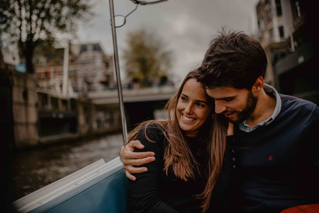 a couple happily in love after the proposal on a canal boat in amsterdam