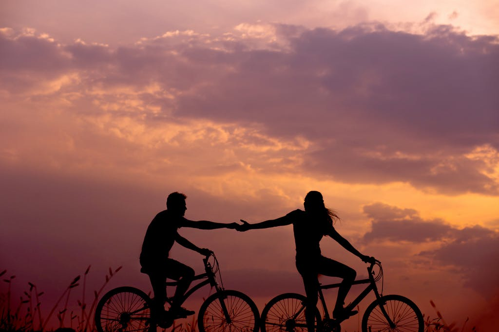 Two people holding hands on a bike at a sunset