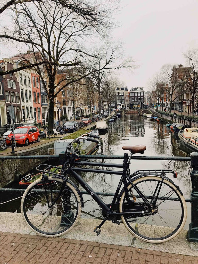 a bicycle parked on the side of an amsterdam canal. explore amsterdam on a bike