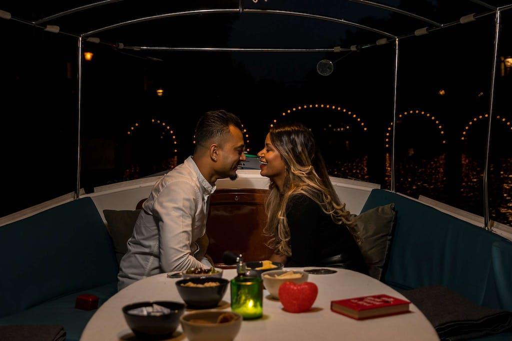 man en vrouw die elkaar zoenen on boot in amsterdam