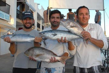 men holding fish they caught