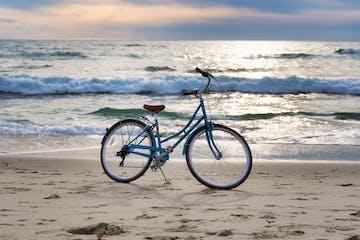 blue bike parked on beach