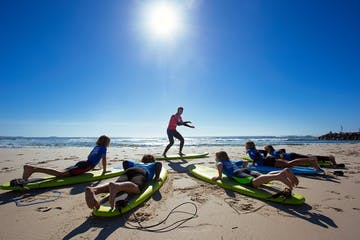 A surf instructor speaking to students at Nudie Surf Groms in Australia
