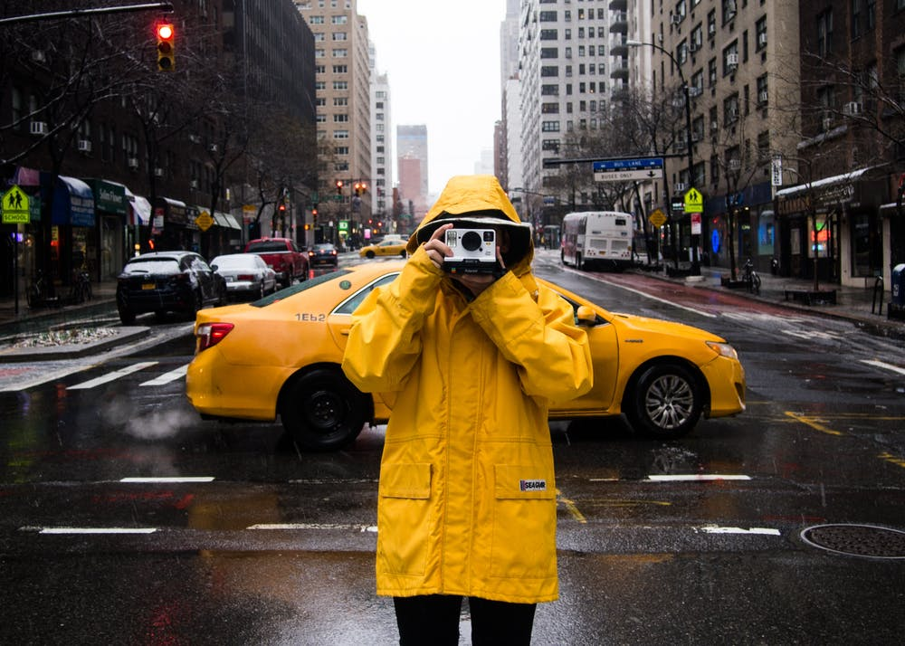 a person crossing the street in the rain