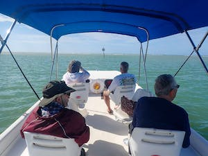 a group of people sitting in a boat on a body of water