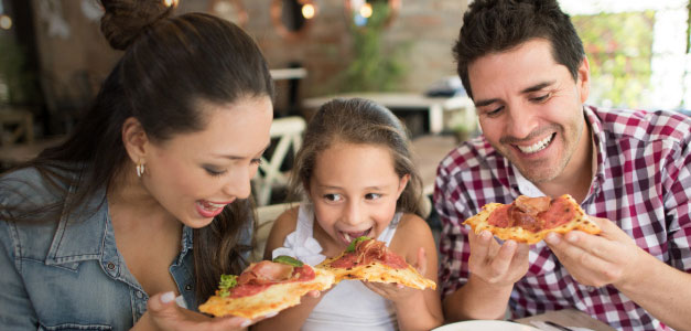 a young girl eating a slice of pizza