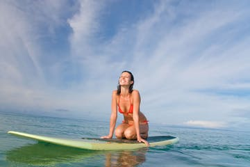 woman kneeling on paddle board and basking in the sun