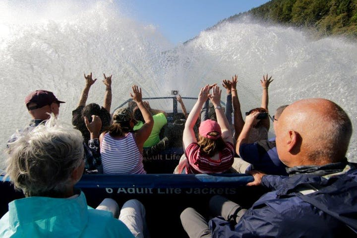 First person view inside the blue jet boat while there is a giant splash in front of them and people with their hands up