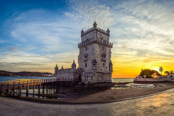 a clock tower on top of a pier with Belém Tower in the background