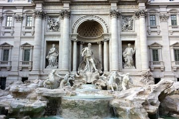 a large stone statue in front of Trevi Fountain