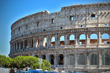 a large stone building with Colosseum in the background