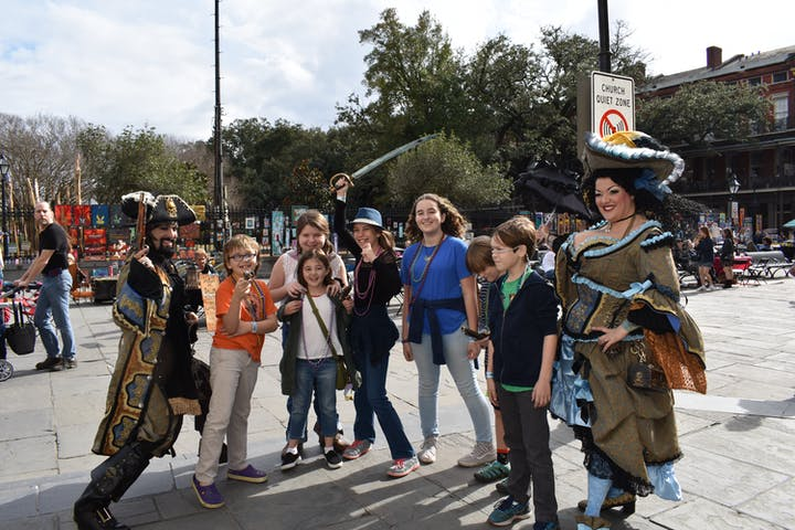 Kids taking photo with people in pirate costumes