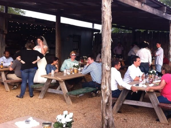 Wedding With Guests Eating at Wooden Tables Under Wooden Canopy