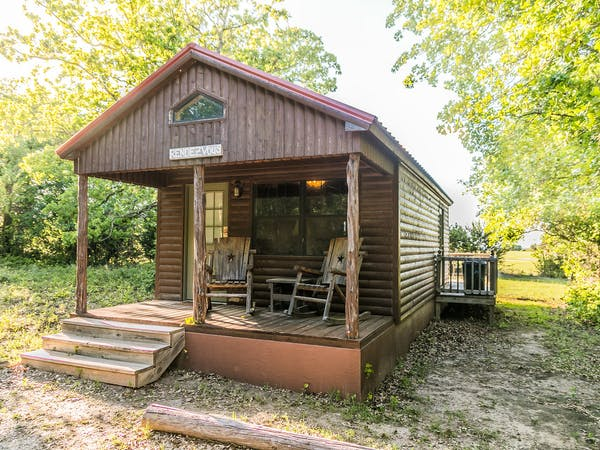 Exterior View of Log Cabin with Front Porch and Two Rustic Rocking Chairs and Side Table and Deck in Background