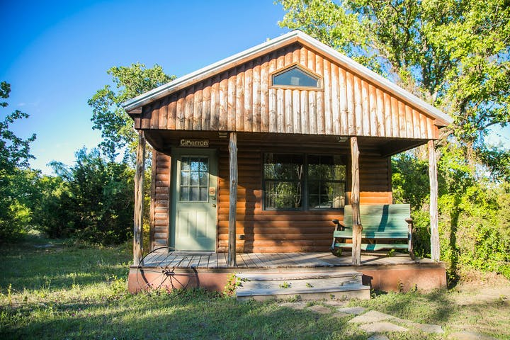 Exterior View of Log Cabin with Front Porch with Green Rocking Bench on it and Old Rustic Wheel