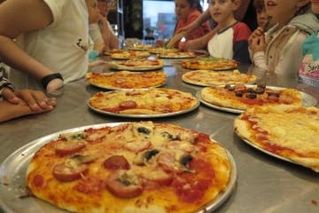 a group of people sitting at a table with a plate of pizza