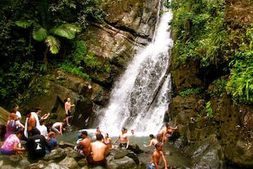 People hanging out in a pool of water in front of a huge waterfall