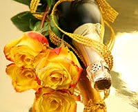 Champagne and yellow roses on gold reflective surface