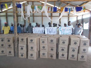 Ugandan refugees hold sign Thank You Capt Dave while standing behind OneMeal boxes of packed food.