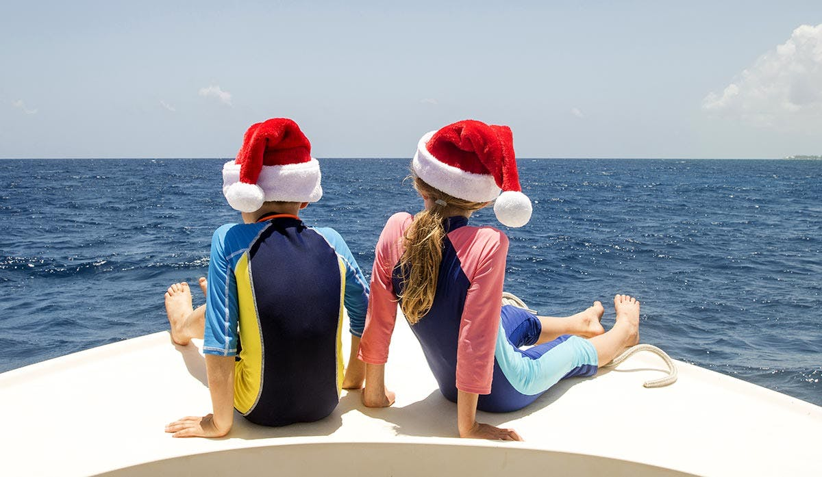 Siblings wearing Santa hats on a boat
