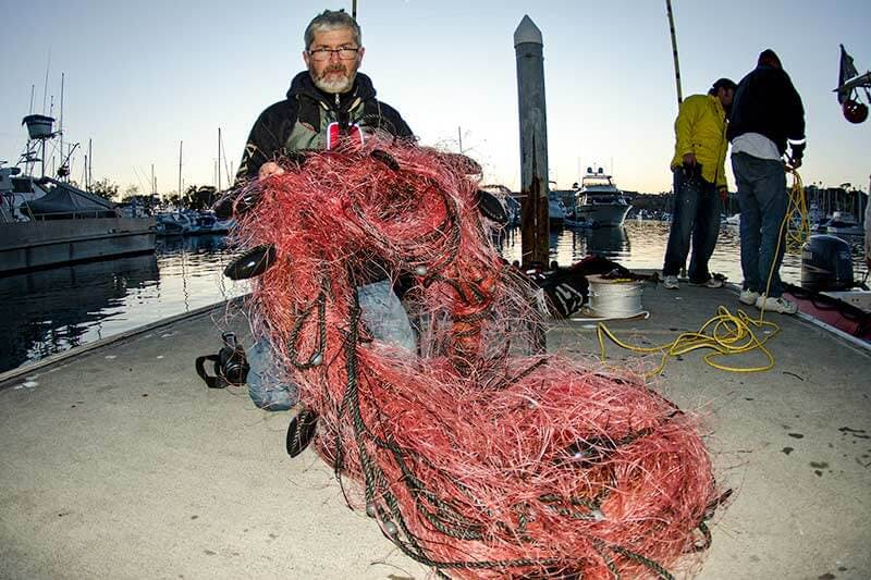 Captain Dave holds up gillnet removed from entangled gray whale