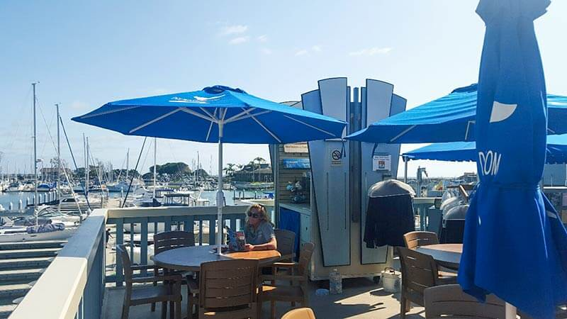 A woman sitting at a table with a blue umbrella on our Dolphin Deck