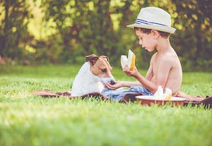 A boy and a dog sitting in the grass having a picnic
