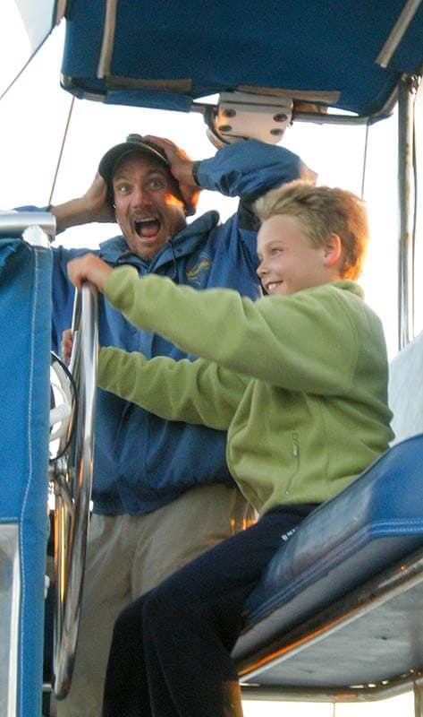 Child passenger at the helm of Manute'a during whale watching trip