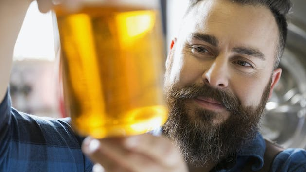 Guy with beard looking at beer