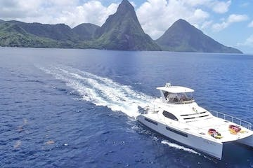 a small boat in a large body of water with Pitons in the background