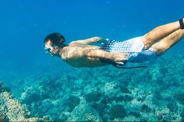 Man swimming above coral reef