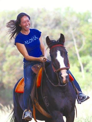 A laughing woman horseback riding