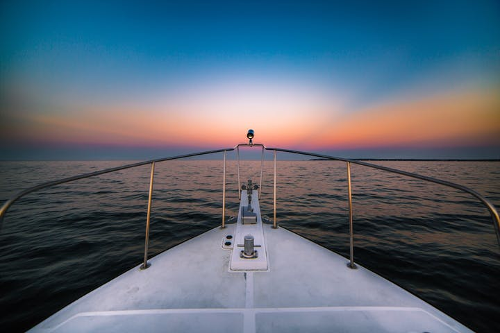 view of sunset from nose of boat