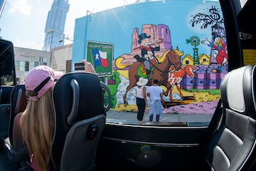 Woman with pink had sitting in AO Tours Austin Panoramic tour bus with monopoly mural in background on a wall