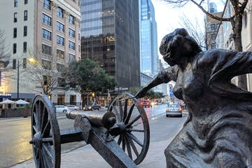 a statue of a woman lighting a cannon on a city street