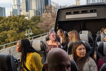 People sitting in panoramic bus with the top open. Austin skyline in the background.