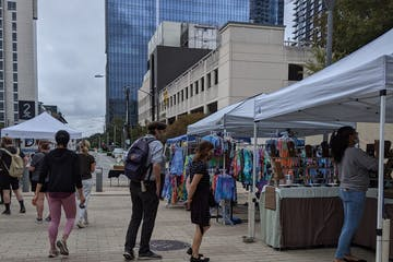 a group of people walking around at SFC farmers market downtown Austin